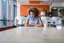 Молода жінка за столом, дивлячись на брошури — стокове фото