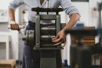 Mittleren Bereich des weiblichen Juweliers schlängelt sich Metallstab durch Maschine in Schmuck-workshop — Stockfoto
