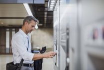 Mature man using ticket machine at train station — Stock Photo