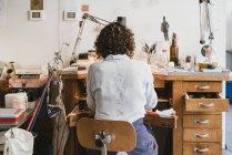 Vue arrière du bijoutier féminin travaillant à l'établi — Photo de stock