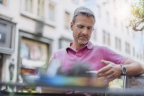 Mature man in outside cafe using smartphone — Stock Photo