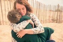 Молода жінка на пляжі обійматися син — стокове фото
