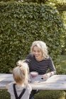 Mother and daughter eating in garden — Stock Photo