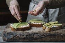 Woman sprinkling chopped walnuts onto avocado bruschetta, mid section — Stock Photo
