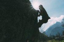 Vue rétroéclairée de jeunes hommes grimpant sur rocher — Photo de stock