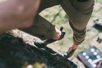 Taille runter Blick auf Mann, der auf Felsbrocken klettert — Stockfoto