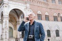Старший мужчина разговаривает по смартфону в городе Сиена, Тоскана, Италия — стоковое фото