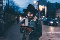 Юнак стояти на вулиці в сутінках, використовуючи цифровий планшетний — стокове фото