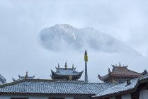 Roofs of Jingang Temple and misty mountain, Kangding, Sichuan, China — Stock Photo