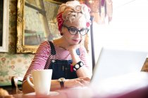 Quirky woman using laptop in bar and restaurant, Bournemouth, England — Stock Photo