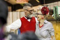 Quirky vintage couple laughing and looking at each other in antique emporium — Stock Photo