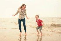 Молодая женщина и сын играет в море — стоковое фото