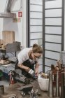 Distant view of Female jeweler pouring liquid into jewelry mold at workbench — Stock Photo