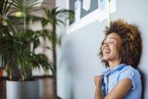 Jeune femme avec des cheveux afro, rire avec les yeux fermés — Photo de stock