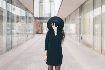 Retrato de jovem mulher em ambiente urbano, cobrindo rosto com chapéu — Fotografia de Stock