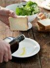 Человек льет оливковое масло на плиту — стоковое фото