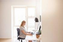 Беременная молодая женщина печатает дома на ноутбуке — стоковое фото