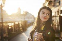 Молодая женщина на открытом воздухе, держа чашку кофе, татуировки на руках и шее — стоковое фото