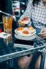 Donna che mangia al marciapiede café, Milano, Italia — Foto stock