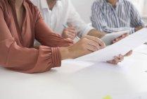 Обрезанный снимок бизнесвумен и мужчин с бумажной работой и цифровым столом в зале заседаний — стоковое фото