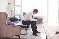 Бизнесмен сидит на кофейном столике и смотрит на смартфон — стоковое фото