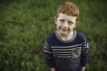 Портрет рыжего мальчика, стоящего на траве — стоковое фото