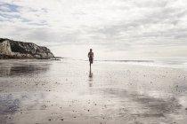 Jeune femme qui court le long de la plage — Photo de stock