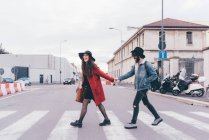 Young couple crossing road, holding hands, laughing — Stock Photo