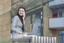 Businesswoman using laptop and making call outdoors — Stock Photo