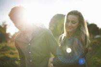 Молодая пара, прогуливающаяся рука об руку на солнечном поле — стоковое фото
