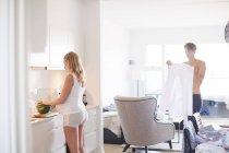 Беременная молодая женщина готовит завтрак, пока муж готовится — стоковое фото