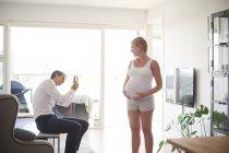 Мужчина делает фото беременной девушки на смартфоне в гостиной — стоковое фото
