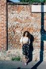 Giovane donna posa contro muro di mattoni — Foto stock