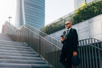 Mature businessman standing on steps with smartphone — Stock Photo