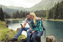 Couple randonnée, assis au bord du lac regardant smartphone, Tyrol, Steiermark, Autriche, Europe — Photo de stock