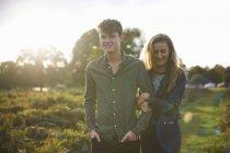 Jovem casal passeando braço a braço no campo — Fotografia de Stock
