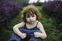 Toddler girl sitting between rows of lavender — Stock Photo