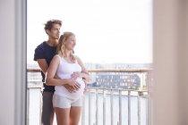 Couple enceinte regardant sur le front de mer depuis le balcon appartement — Photo de stock