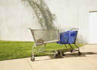 Two shopping trollies touching each other — Stock Photo