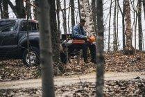 Masculino logger sentado no pegar caminhão e segurando Difícil chapéu — Fotografia de Stock