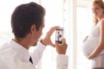Sopra la spalla vista di uomo scattare foto di fidanzata incinta — Foto stock