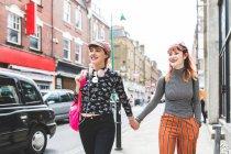 Deux jeunes femmes au style rétro se promenant dans la rue de la ville — Photo de stock