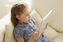 Jeune fille relaxante sur canapé avec tablette numérique — Photo de stock
