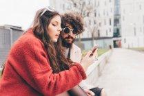 Coppia giovane seduta all'aperto, guardando lo smartphone — Foto stock