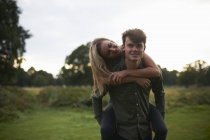 Young man giving girlfriend on piggyback in field — Stock Photo