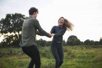 Jovem casal de mãos dadas e girando uns aos outros em campo — Fotografia de Stock
