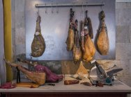 Iberico Ham hanging from meat hooks above kitchen counter, Catalonia, Spain — Foto stock