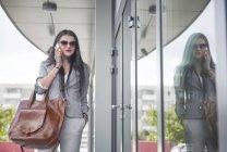 Бізнес-леді поблизу офісної будівлі за допомогою смартфона — стокове фото
