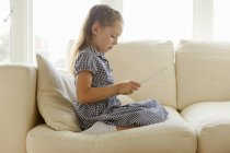Young girl sitting on sofa with digital tablet — Stock Photo
