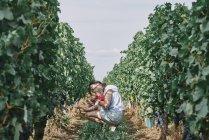 Вид сбоку на женщину с маленькой дочкой в винограднике — стоковое фото